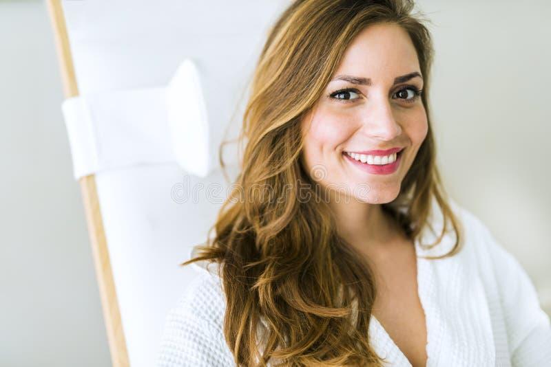 Porträt einer schönen jungen Frau, die in einer Robe sich entspannt stockfoto