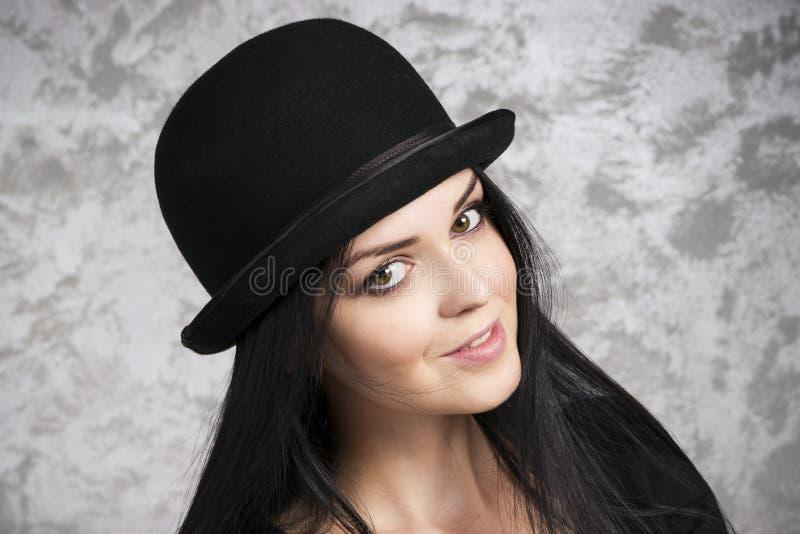 Porträt einer schönen jungen Frau in einer Melone stockbilder