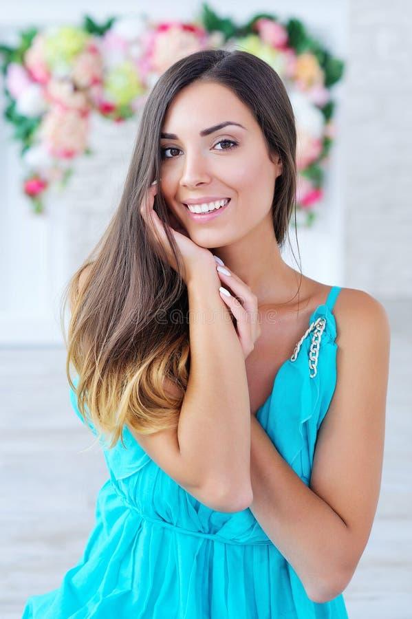 Porträt einer schönen jungen Frau mit Blumenhintergrund lizenzfreie stockfotos