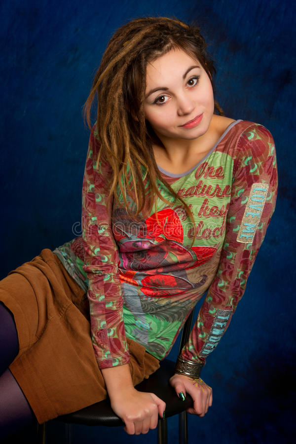 Junge Frau mit dreadlocks gegen einen blauen Hintergrund stockfotos