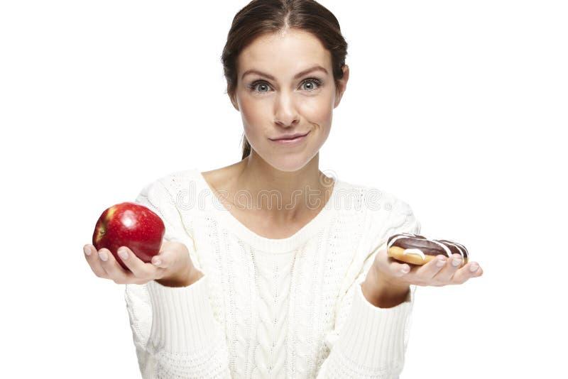 Porträt einer schönen jungen Frau, wählend zwischen Apfel und Donut lizenzfreie stockfotos