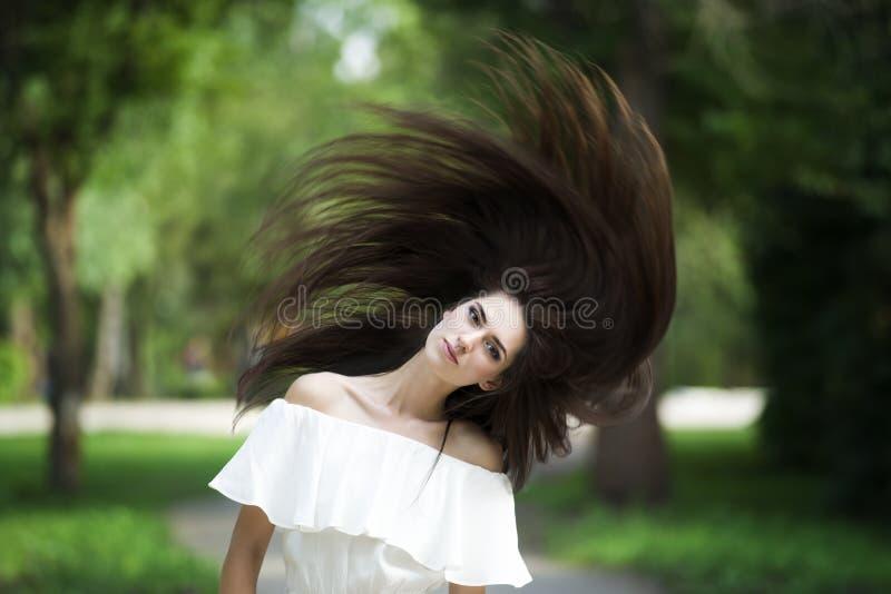 Porträt einer schönen jungen kaukasischen Frau mit dem Fliegen des langen Haares, der sauberen Haut und des zufälligen Makes-up stockfoto