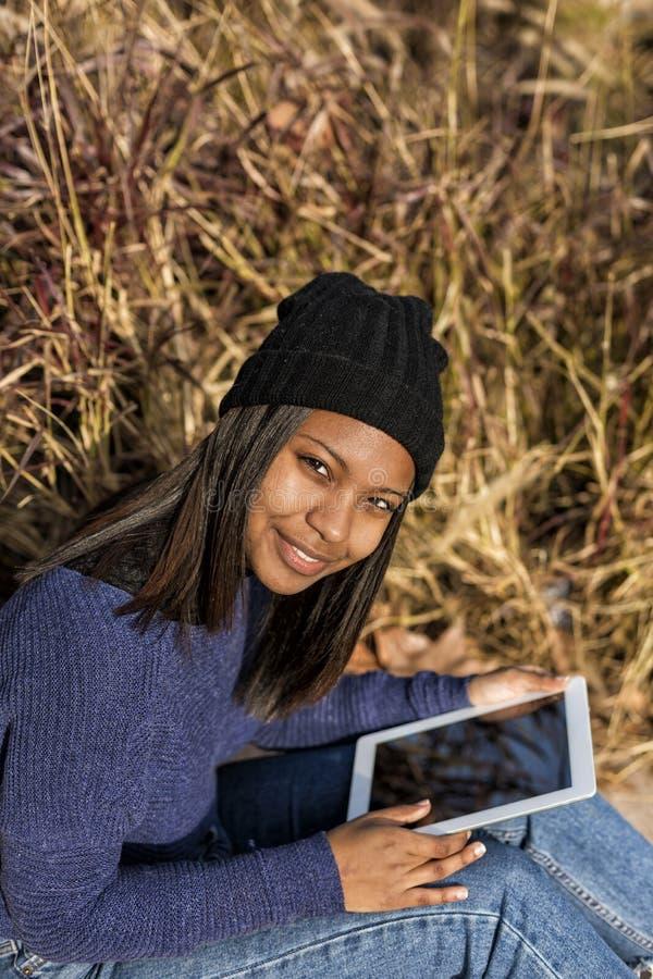 Porträt einer schönen jungen lächelnden afrikanischen Frau, die den Tabletten-PC-Computer sitzt in der Stadt an einem sonnigen Ta stockfotos