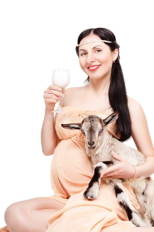 Porträt einer schönen jungen schwangeren Frau mit einer Ziege stockfotografie