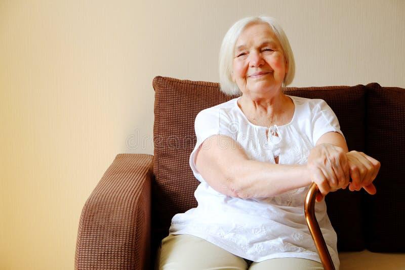 Porträt einer schönen lächelnden älteren Frau mit gehendem Stock auf hellem Hintergrund zu Hause lizenzfreies stockbild