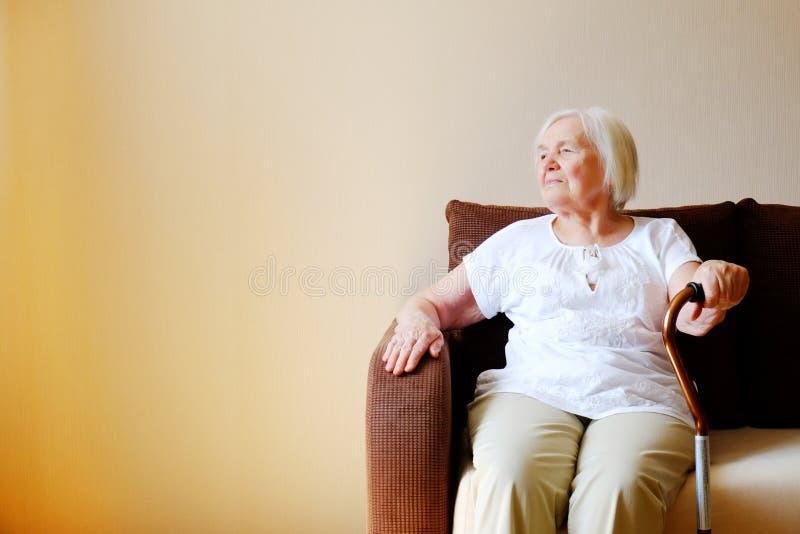 Porträt einer schönen lächelnden älteren Frau mit gehendem Stock auf hellem Hintergrund zu Hause stockfotografie