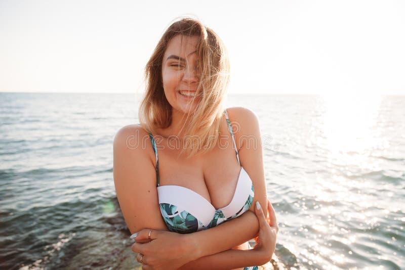 Porträt einer schönen lächelnden jungen Frau im Bikini auf dem Strand Weibliches Modell, das im Badeanzug auf Seeufer aufwirft Gl lizenzfreie stockbilder
