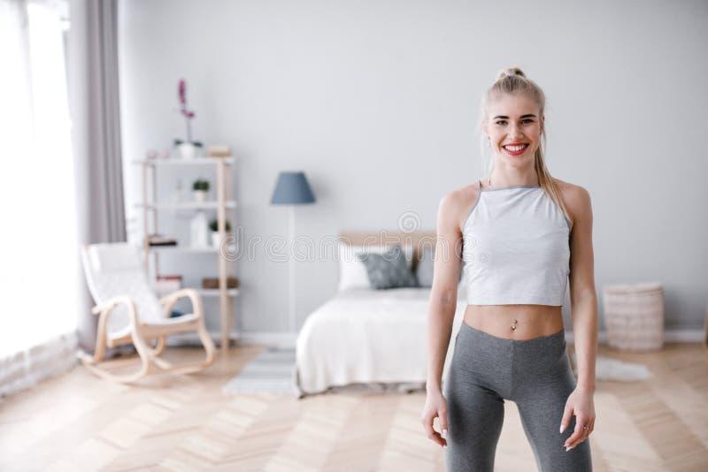 Porträt einer schönen lächelnden sportlichen Frau zu Hause stockbilder