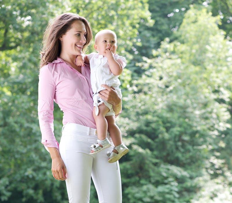 Porträt einer schönen Mutter, die Baby im Park hält lizenzfreie stockbilder