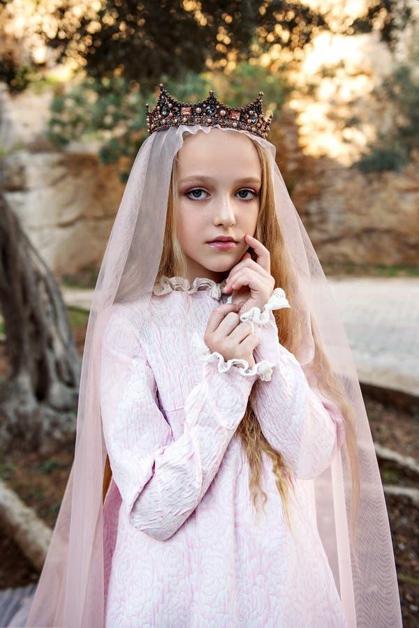 Porträt einer schönen Nymphenkönigin der weißen Hexen in ihrem Hochzeitskleid mit einem Schleier in der Krone im magischen Wald lizenzfreie stockbilder