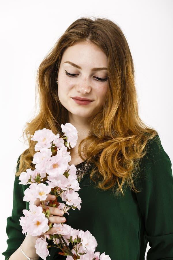Porträt einer schönen rothaarigen Frau, die eine Blume in ihr hält stockbild