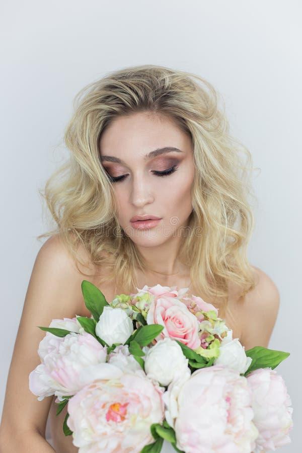 Porträt einer schönen sexy jungen Frau mit hellem Make-up mit den bloßen Schultern, die einen großen Blumenstrauß in den Händen a lizenzfreie stockfotografie