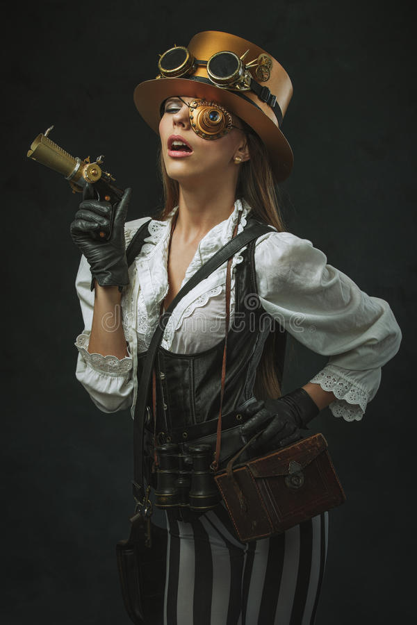 Porträt einer schönen steampunk Frau, die ein Gewehr hält stockfotos