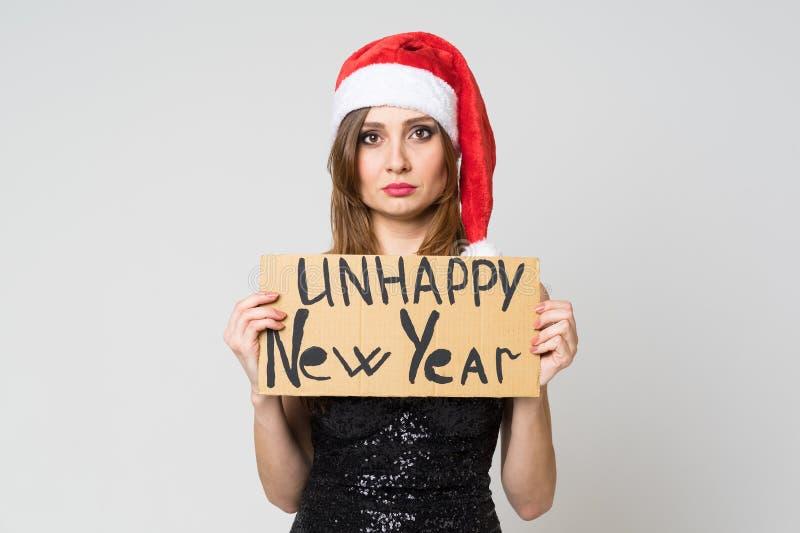 Portr?t einer sch?nen traurigen brunette Frau im Weihnachtshut und in festlichem schwarzem Kleid, die ein Pappzeichen ?ungl?cklic lizenzfreie stockfotos