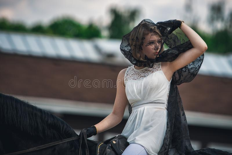 Porträt einer Schönheit, die ein Pferd reitet mitfahrer lizenzfreies stockfoto