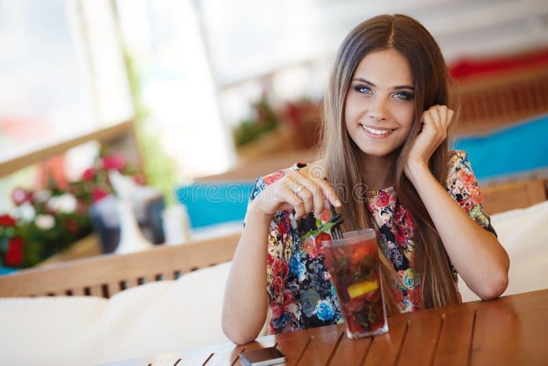 Porträt einer Schönheit an einem Tisch im Sommercafé lizenzfreies stockbild