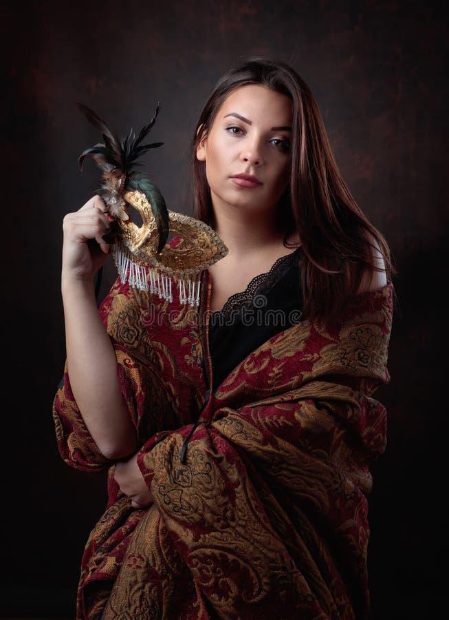 Porträt einer Schönheit mit goldener Karnevalsmaske lizenzfreie stockfotos