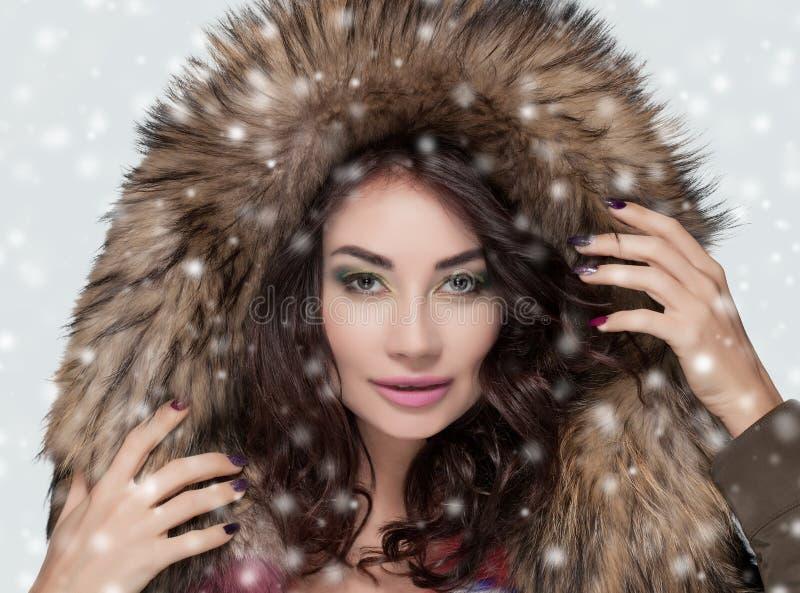 Porträt einer Schönheit mit schönem Make-up und der Maniküre in einem Pelzmantel lizenzfreie stockfotografie