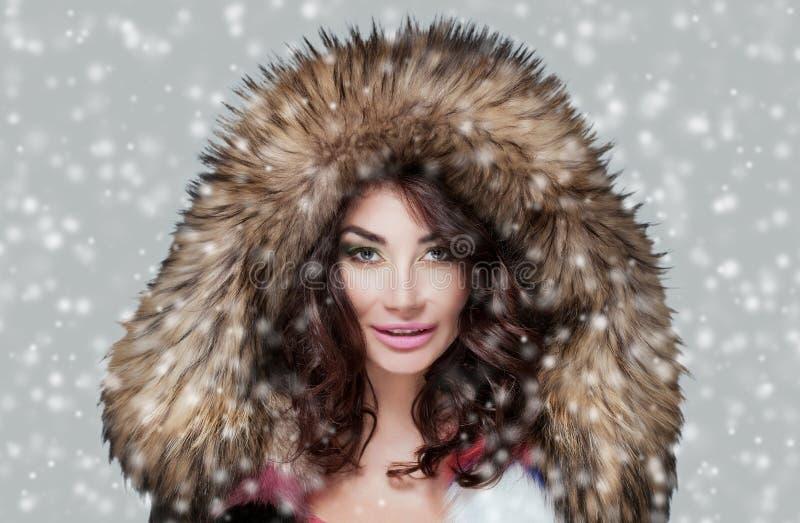 Porträt einer Schönheit mit schönem Make-up und der Maniküre in einem Pelzmantel auf einem Hintergrund des Schnees lizenzfreie stockfotografie