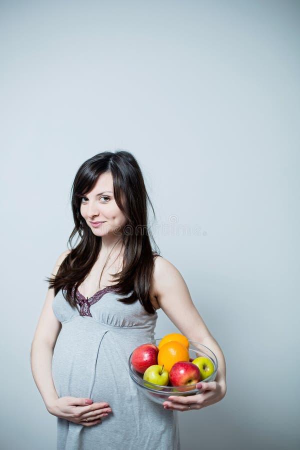 Porträt einer schwangeren Frau mit bunter Frucht lizenzfreie stockfotografie