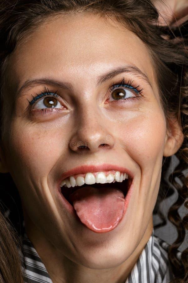 Porträt einer sinnlichen schönen jungen Frau, die lange Zunge zeigt lizenzfreie stockbilder