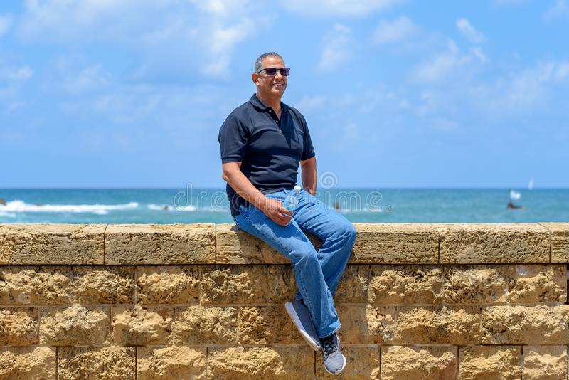 Porträt einer sitzenden Außenseite des überzeugten reifen Geschäftsmannes stockfoto