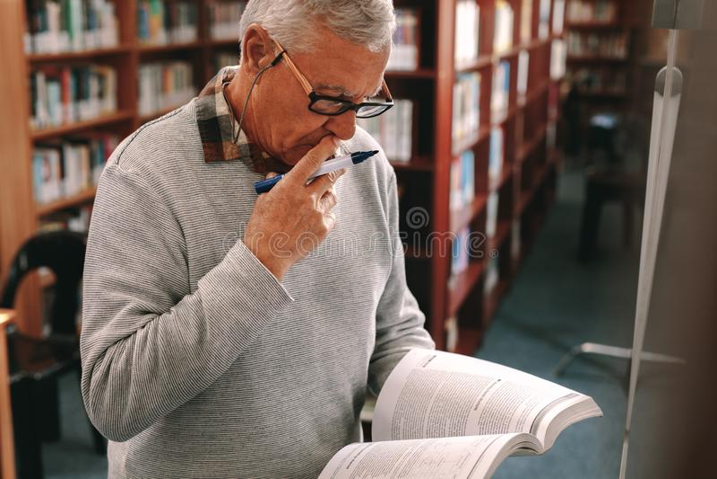 Porträt einer Stellung des älteren Mannes in der Klasse, die ein Lehrbuch hält lizenzfreie stockfotografie