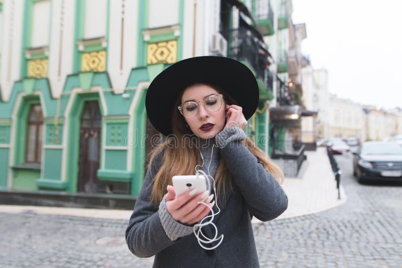 Porträt einer stilvollen Frau, die Musik in den Kopfhörern auf dem Hintergrund einer schönen alten Stadt hört lizenzfreie stockfotografie