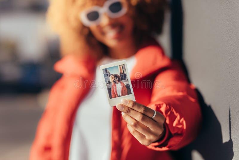 Porträt einer touristischen Frau, die ein polaroidfoto hält stockbild