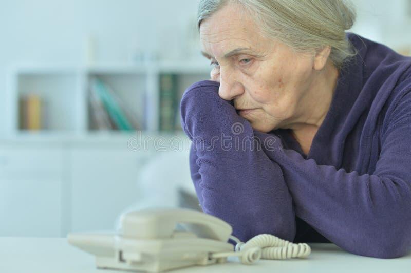 Porträt einer traurigen älteren Frau, die Telefon betrachtet lizenzfreies stockbild