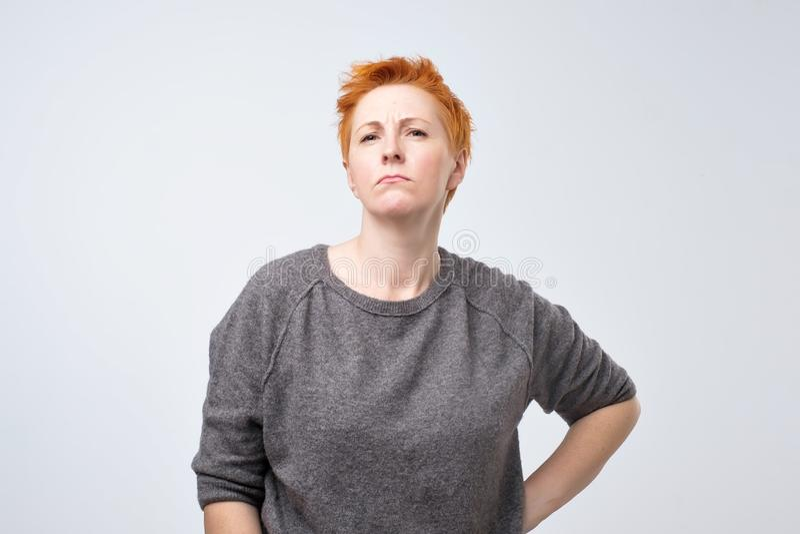Porträt einer traurigen Frau von mittlerem Alter mit dem kurzen roten Haar auf einem grauen Hintergrund stockfotografie