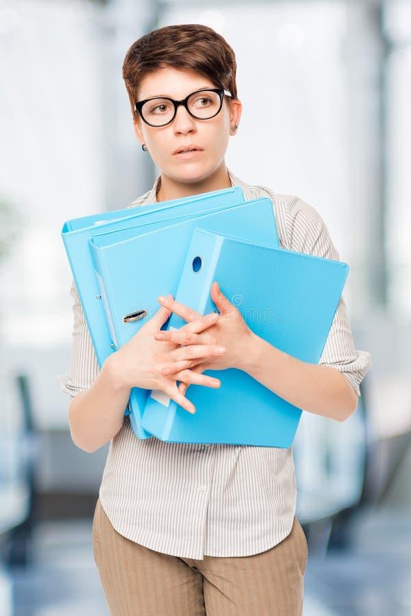Porträt einer verwirrten Frau mit einem Ordner in den Händen lizenzfreie stockfotografie