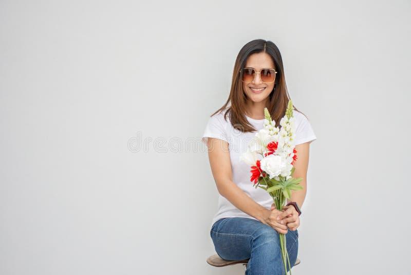 Porträt einer wunderschönen Asiatischen Frau mit Sonnenbrille, die mit einem Blumenstrauß auf weißem Grund Kamera ansieht stockbilder