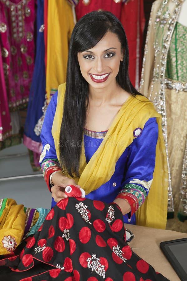 Porträt einer zusammenpassenden Threadfarbe der indischen weiblichen Damenschneiderin mit dem Stoff stockfoto