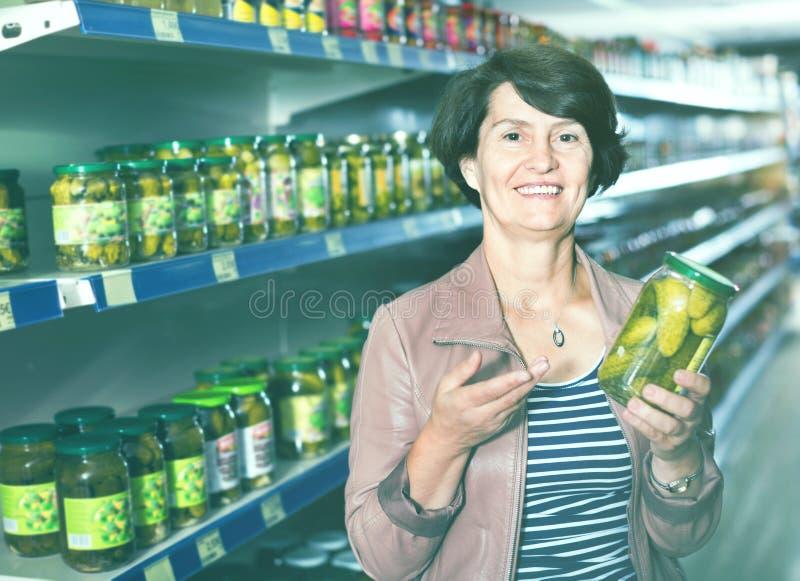 Porträt eines älteren Frauenkaufens Gurken stockfotografie