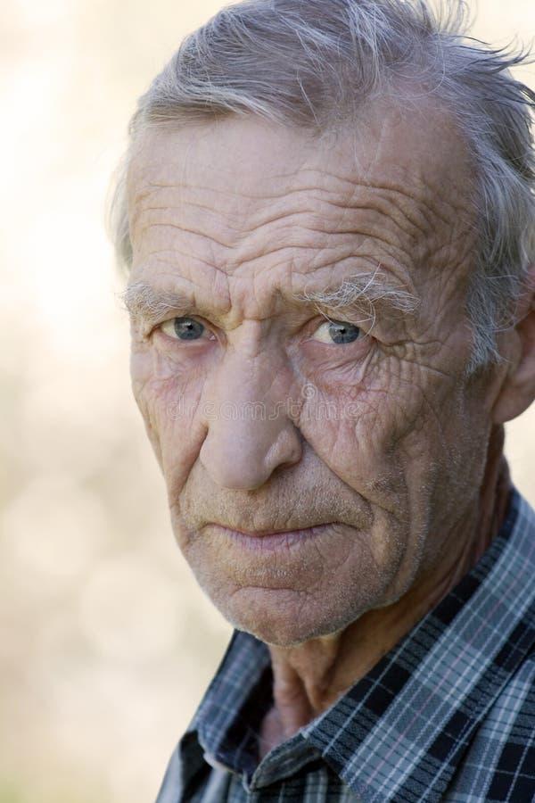 Porträt eines älteren Mannes, der entlang Sie anstarrt lizenzfreies stockbild