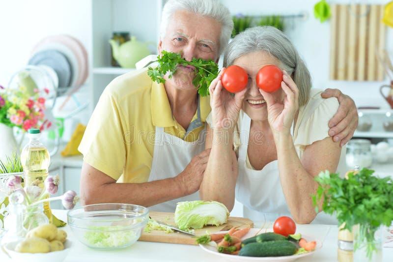 Porträt eines älteren Paares, das in der Küche kocht lizenzfreie stockfotografie
