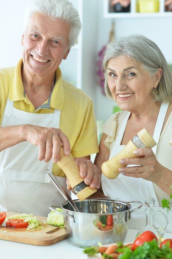 Porträt eines älteren Paares, das in der Küche kocht stockfotografie