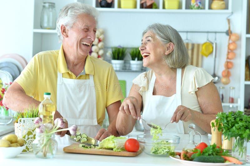 Porträt eines älteren Paares, das in der Küche kocht lizenzfreie stockfotos