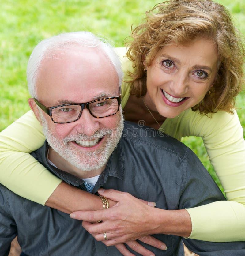 Porträt eines älteren Paares, das zusammen draußen lächelt lizenzfreie stockfotografie