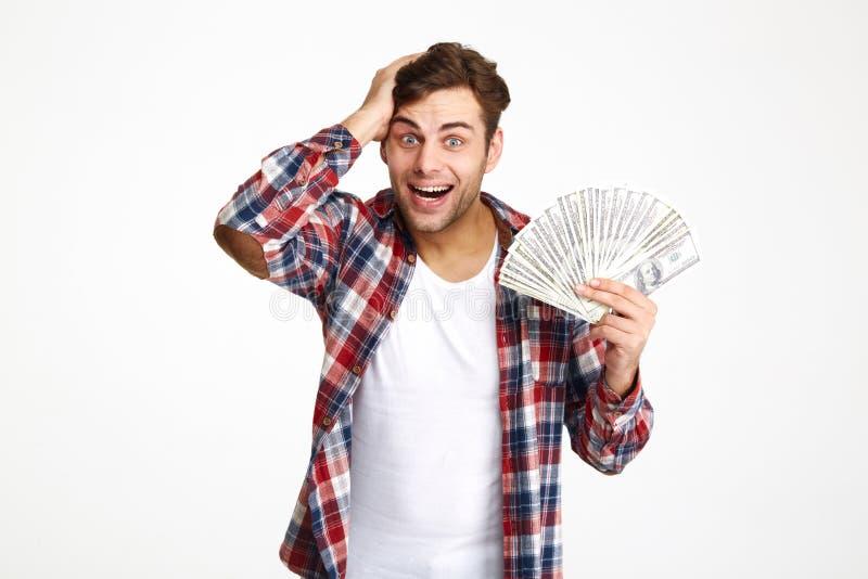 Porträt eines überwältigten aufgeregten Mannes, der Bündel Geld hält lizenzfreies stockfoto