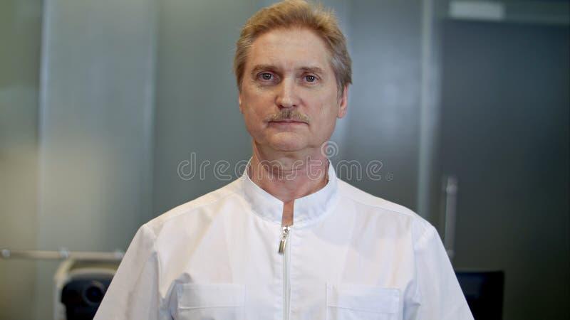 Porträt eines überzeugten älteren Doktors, der am Krankenhaus beim Betrachten der Kamera steht stockbilder