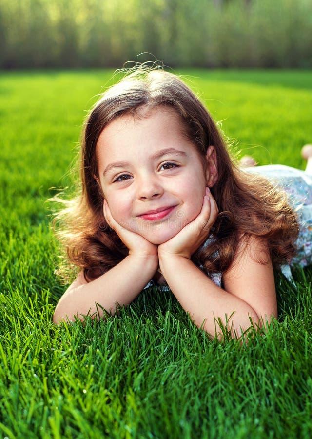 Porträt eines adorbale Kindes, das auf einen frischen, grünen Rasen legt stockfotos