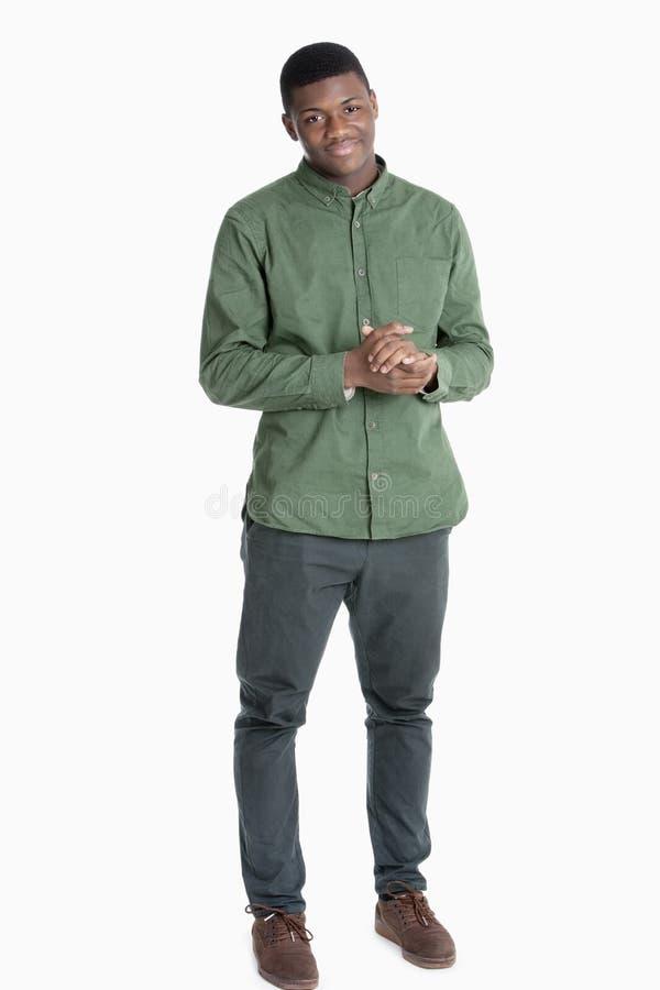 Porträt eines Afroamerikanermannes, der mit den Händen umklammert über grauem Hintergrund steht lizenzfreie stockfotografie