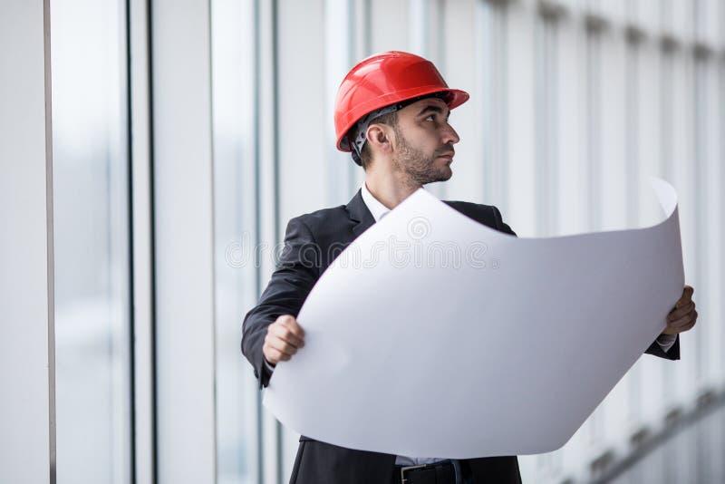 Porträt eines Architektenerbauers, der Planplan des Gebäudes, ernsten Bauingenieur an arbeitet mit Dokumenten studiert stockfotografie