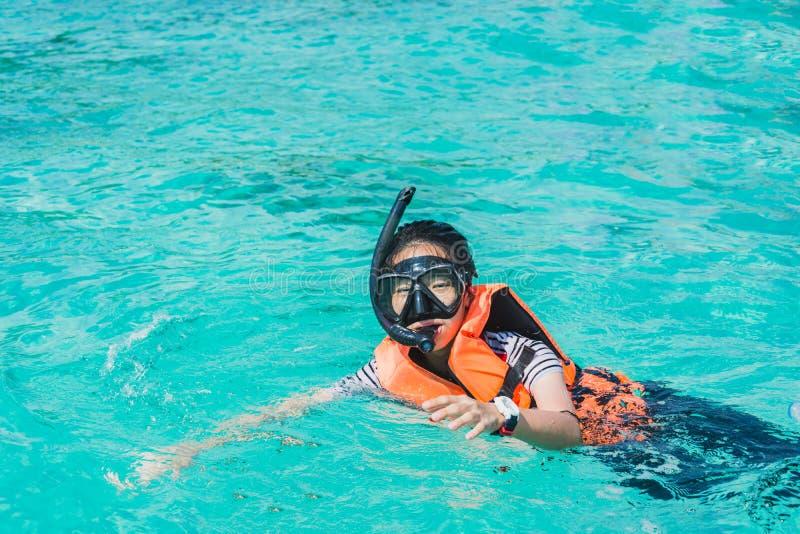 Porträt eines asiatischen schnorchelnden Mädchens mit Maskenschwimmen auf dem Se stockbild