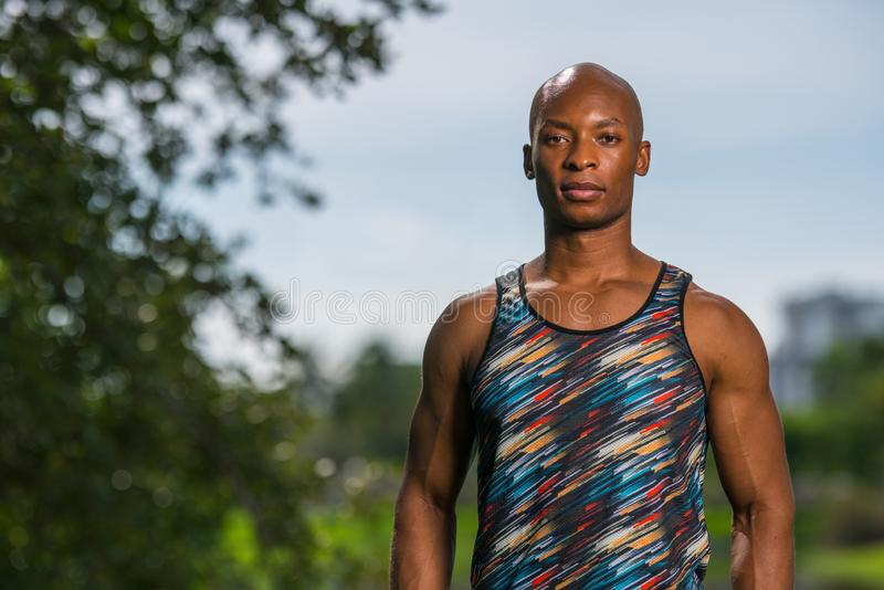 Porträt eines athletischen schwarzen Mannes mit dem abstrakten farbigen Hemd, das draußen im Park aufwirft stockfotografie