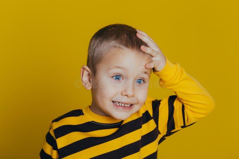 Porträt eines attraktiven durchdachten Jungen in einer gestreiften Strickjacke, die eine Hand auf seinem Kopf auf einem gelben Hi lizenzfreie stockfotografie