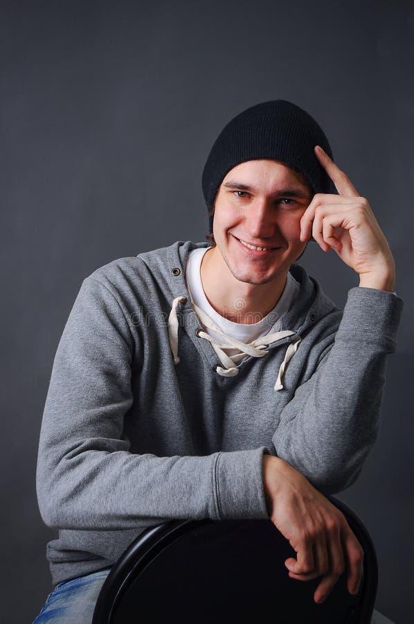 Porträt eines attraktiven jungen männlichen Modells im schwarzen Hut, in den Jeans und im grauen Sweatshirt, Studio, dunkelgrauer lizenzfreie stockfotos