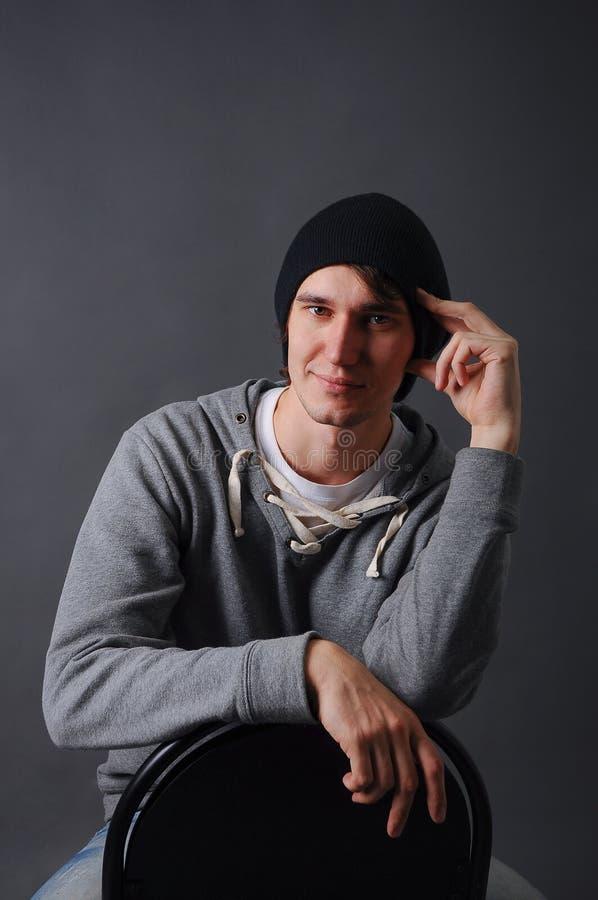 Porträt eines attraktiven jungen männlichen Modells im schwarzen Hut, in den Jeans und im grauen Sweatshirt, Studio, dunkelgrauer stockbilder
